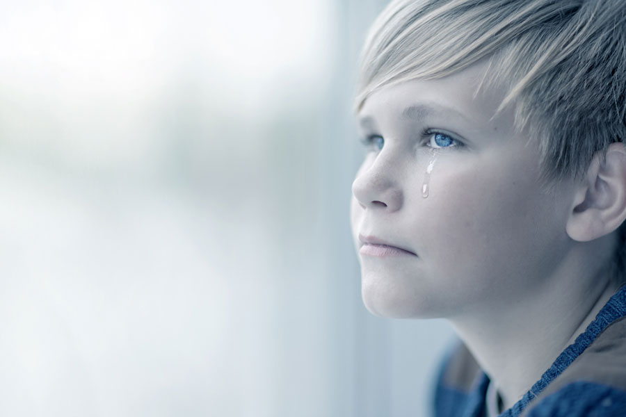 Teenager crying at a window