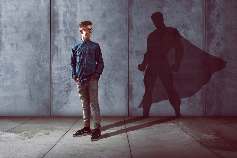 Teenage boy with superhero shadow