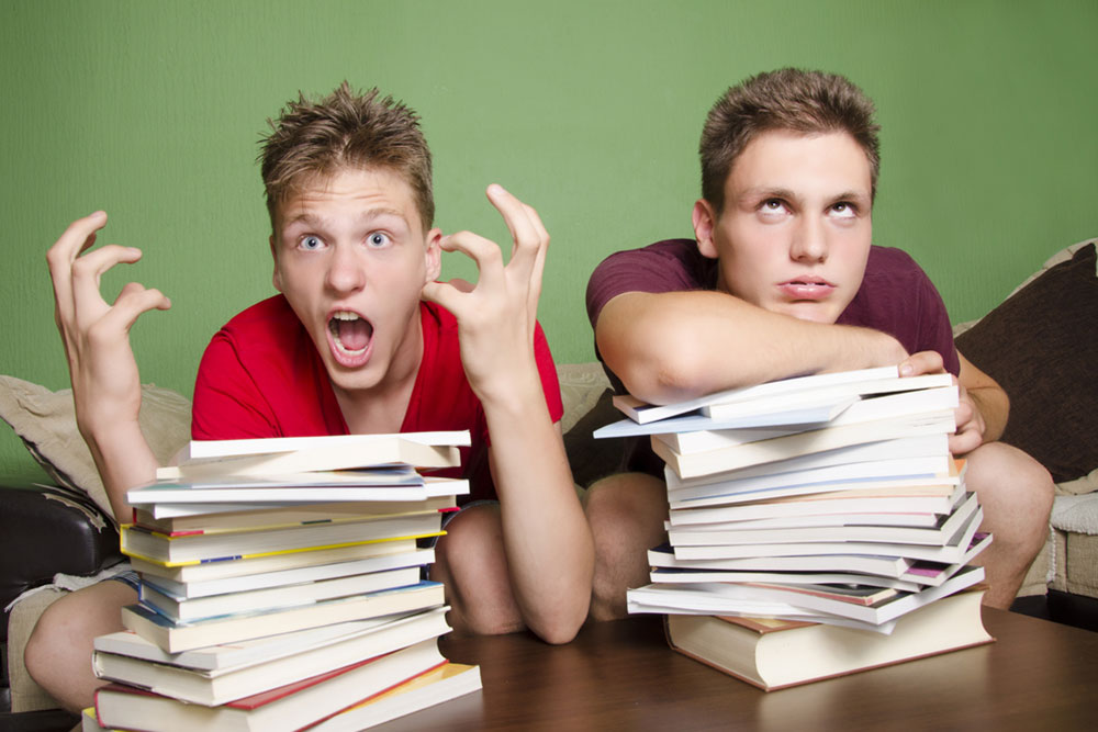 Two teenagers with stacks of homework feeling overwhelmed