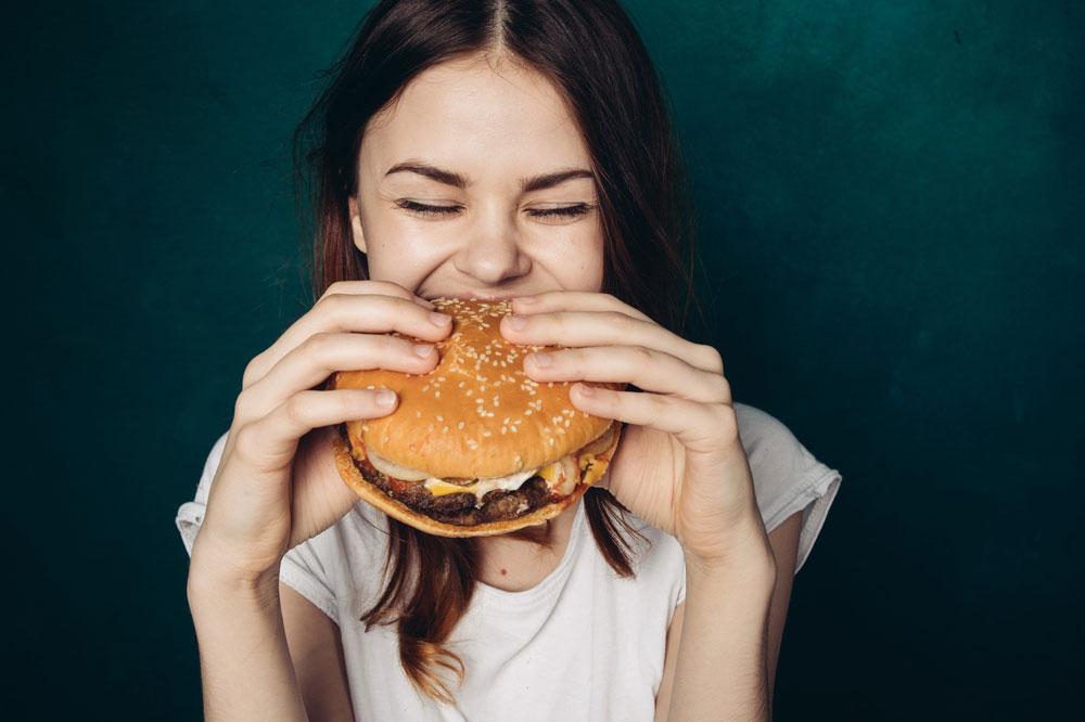 Teenage girl eating large burger