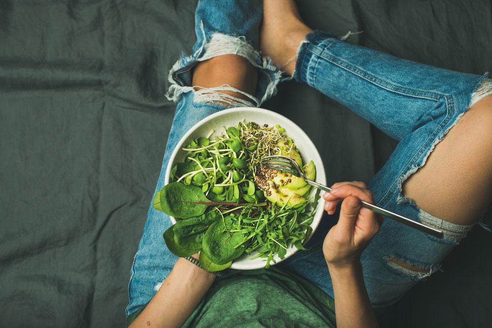Female teenager sat on floor eating a vegan salad