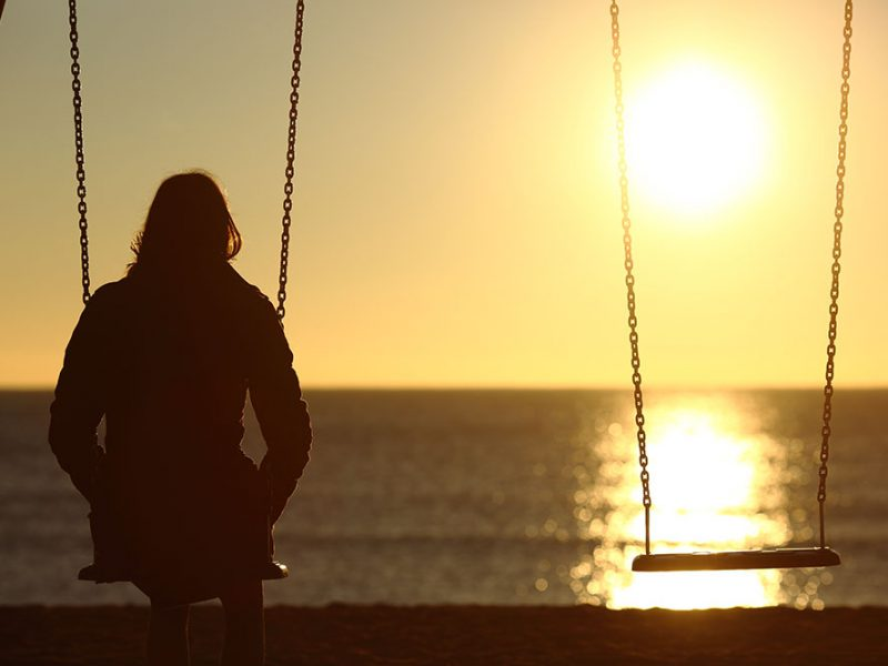 Woman sitting alone on a beach with her negative thoughts watching the sunset.