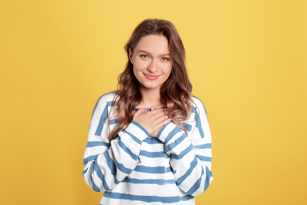 Girl in striped top with hand over chest