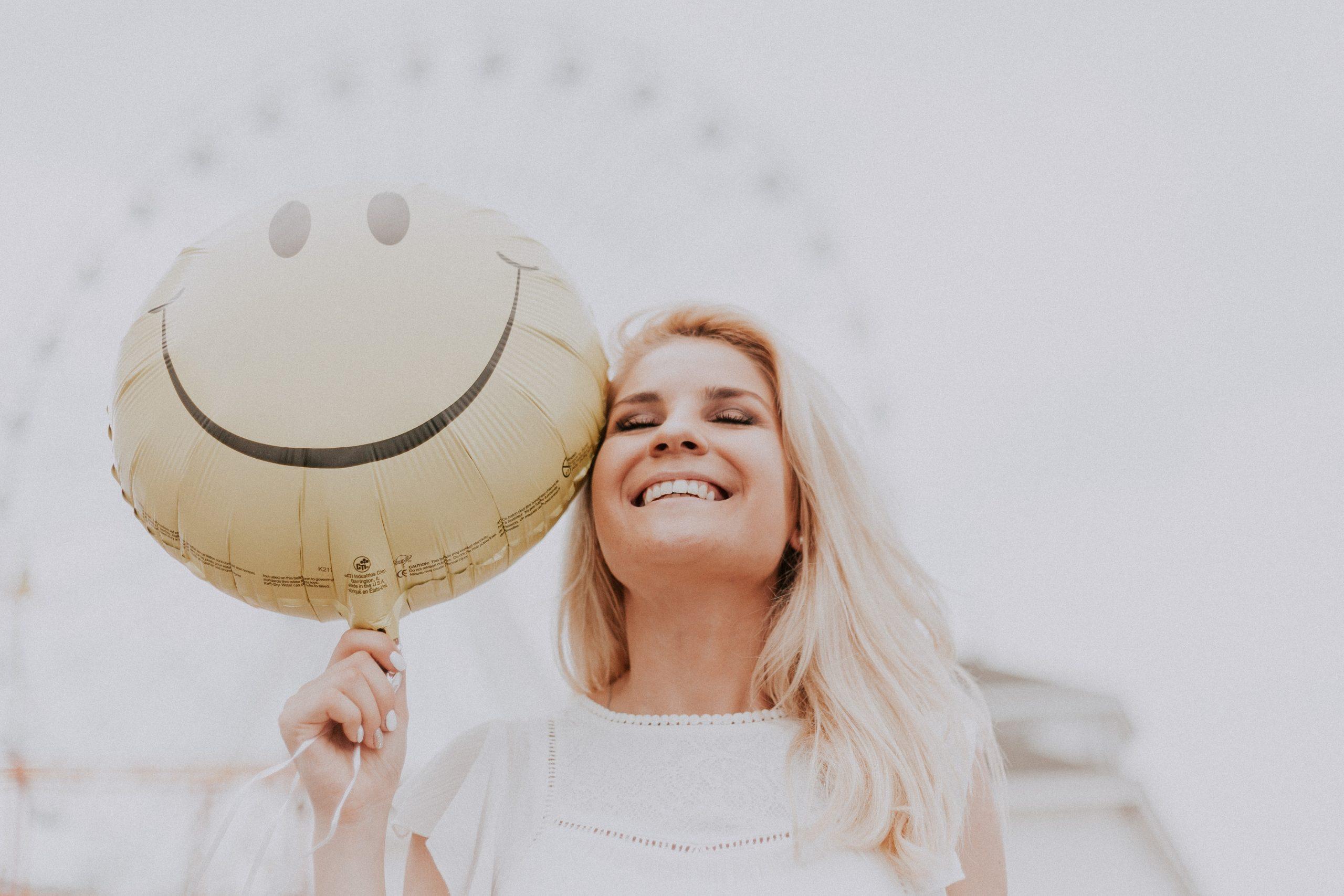 Girl holding balloon smiling