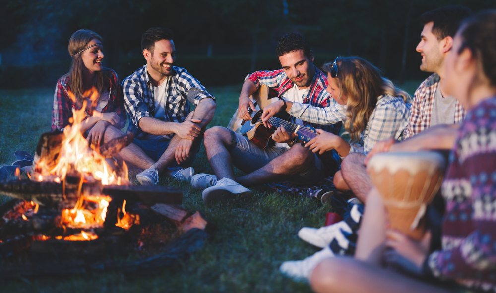 Group of friends sitting around a camp fire