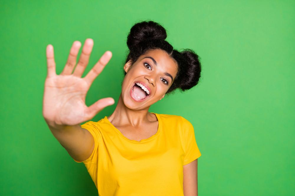 Happy girl in yellow top waving