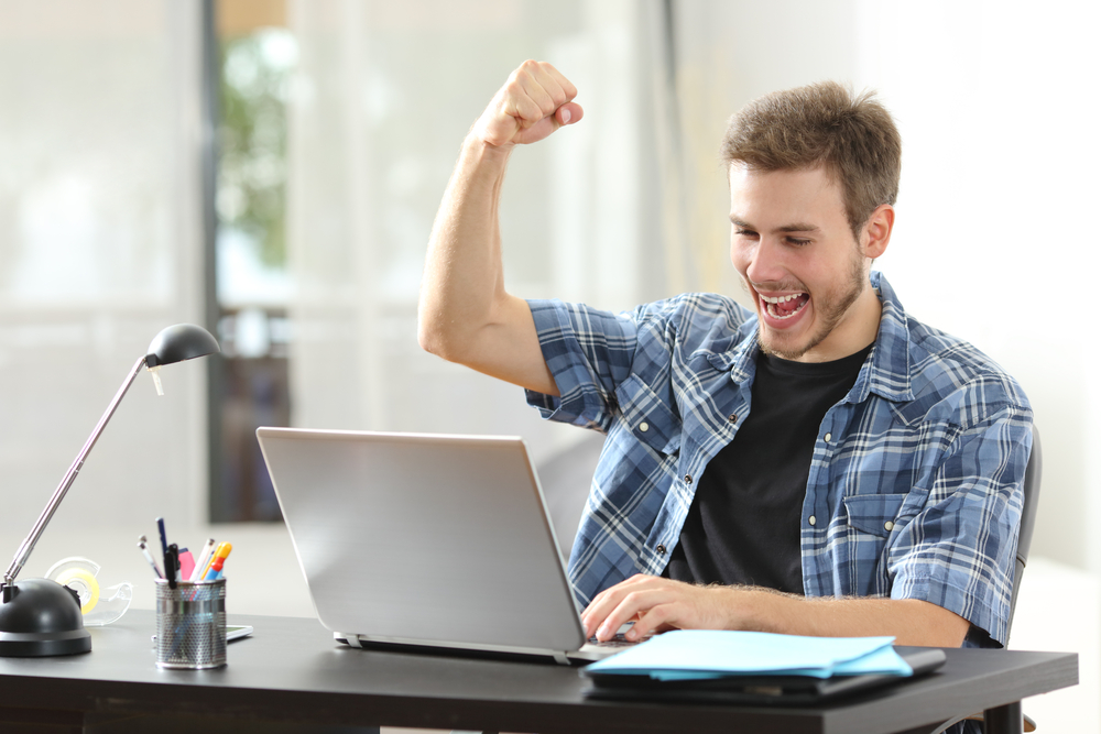 Teenager happy at a laptop