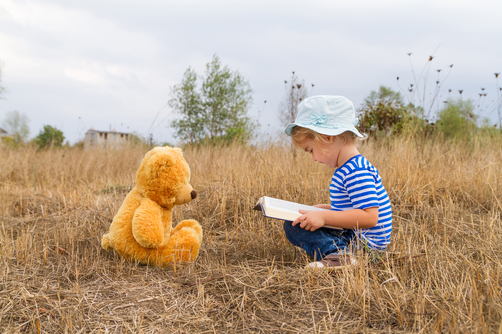 Young child reading a book to a teddy