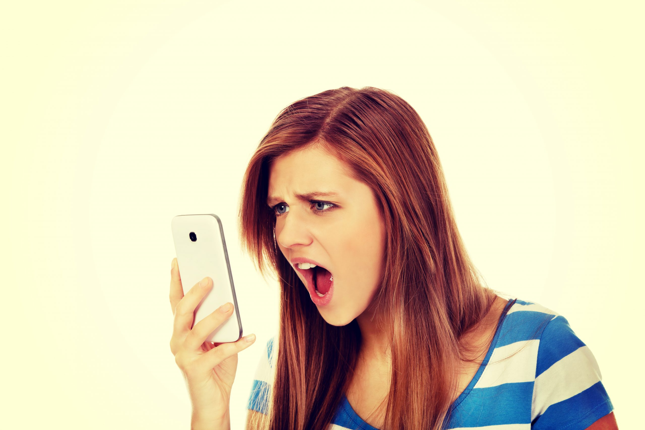 Angry young female teenager looking at her phone.
