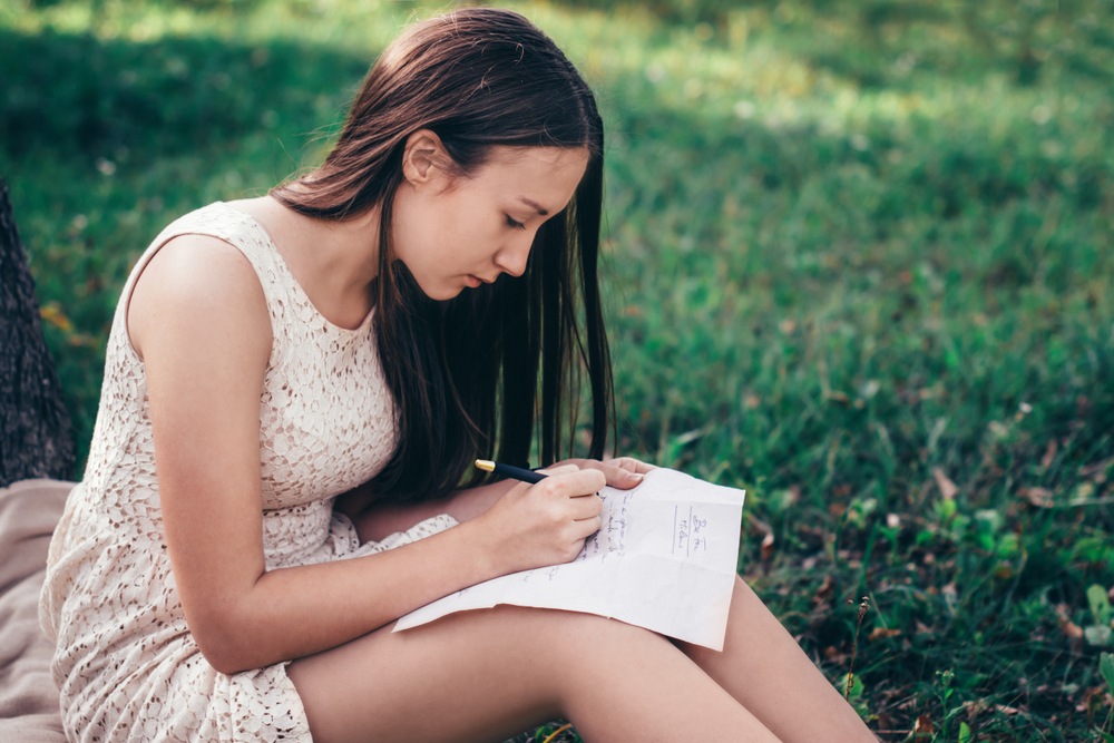 Girl writing a letter on the grass