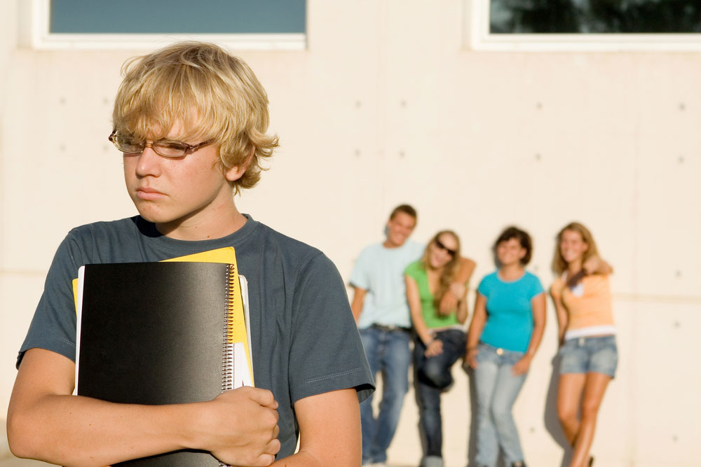 Isolated teenage boy in the forground with fellow 'popular' high school pupils learning against the wall staring on the background.