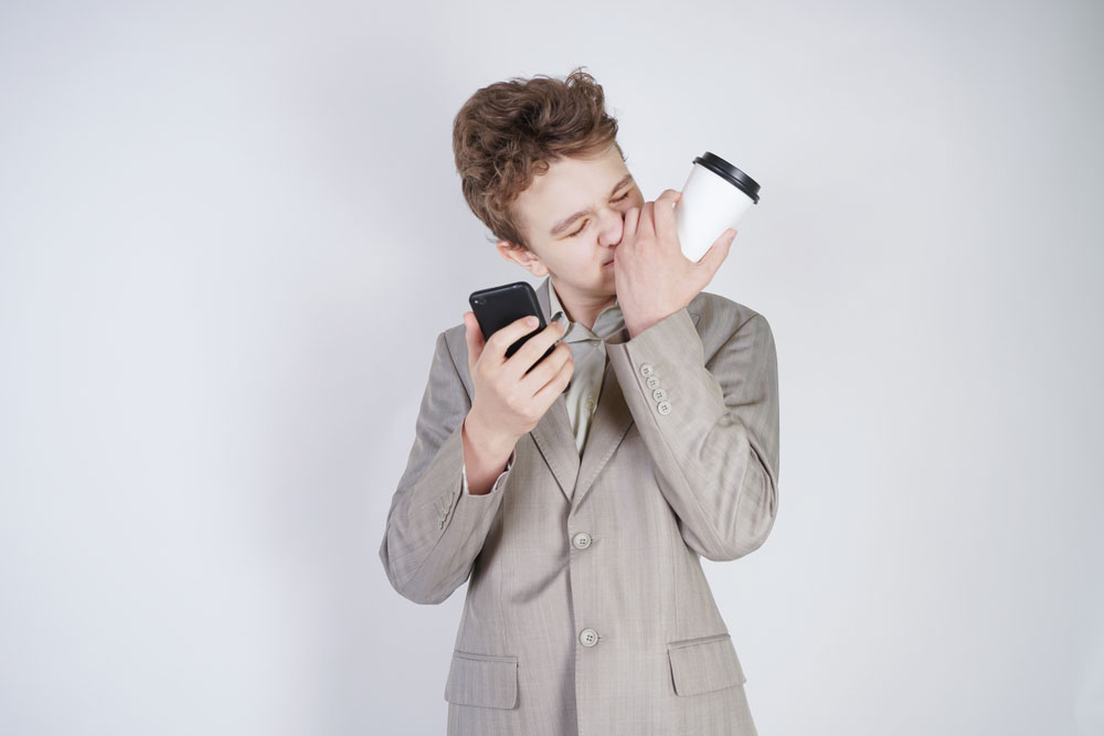 Male teenager holding a cup as he lies on the the phone to a friend