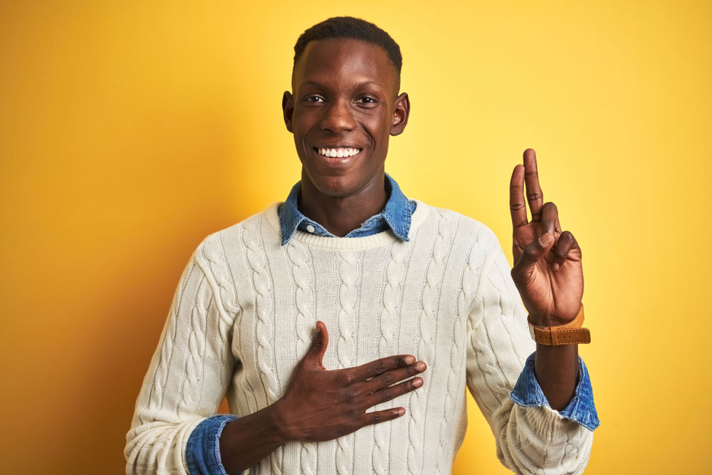 Young black male making the promises hand sign