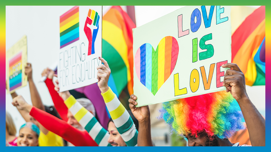 People hold love in love sign at a Pride event in England