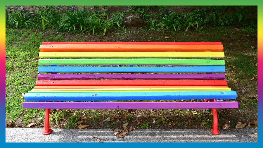Park bench painted in the LGBT rainbow colours