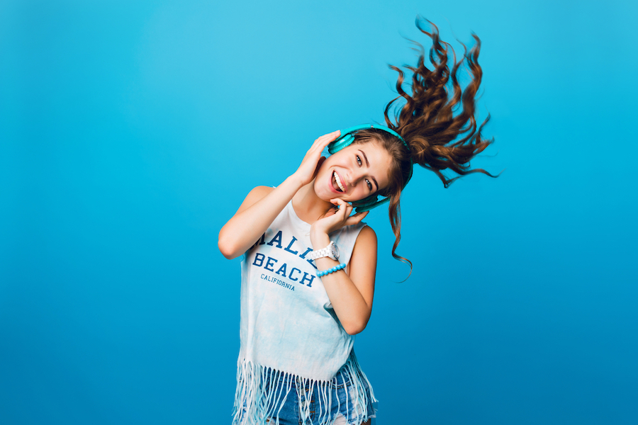 Girl with headphones dancing in front of a blue background