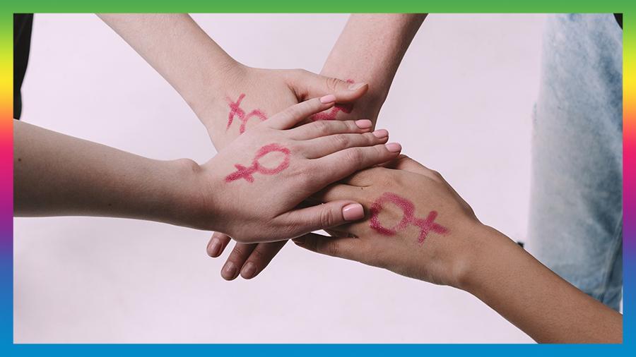 Three hands together symbolising Feminism and sisterhood