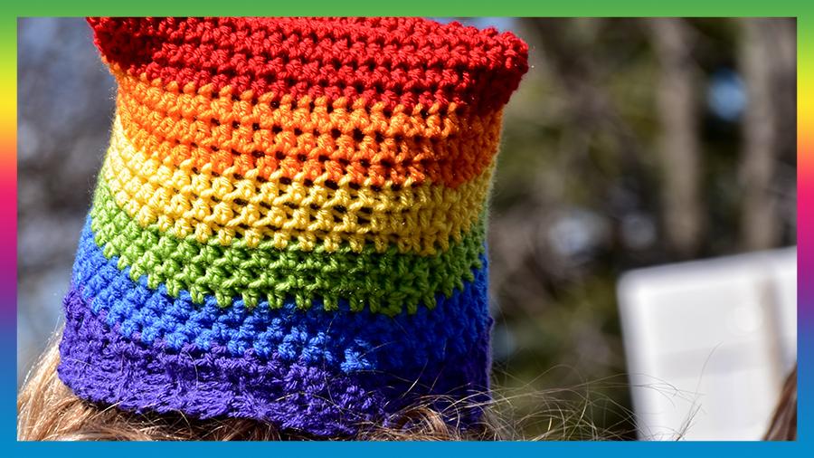 Woman wearing LGBT crocheted hat